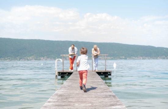 Couple sur un ponton avec leur petit garçon qui cours vers eux